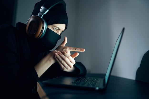 Mulher com máscara na frente do laptop hackeando fones de ouvido