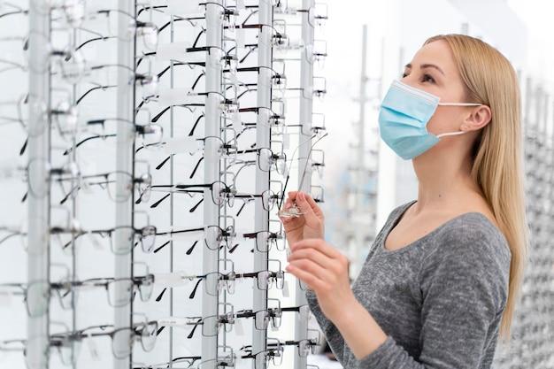 Mulher com máscara na loja experimentando óculos