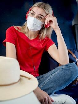 Mulher com máscara ouvindo música enquanto viaja