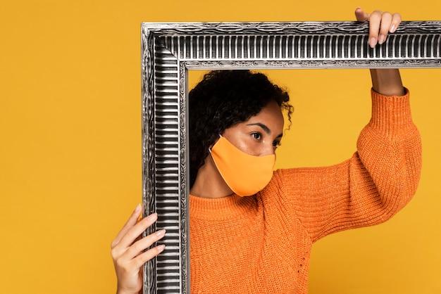 Mulher com máscara posando com moldura