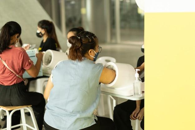Mulher com máscara protetora de inserção de braço para medição automática de máquina de pressão arterial e frequência cardíaca