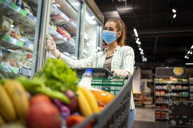 Mulher com máscara protetora e luvas comprando em supermercado durante a pandemia de covid-19 ou vírus corona