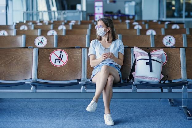 Mulher com máscara protetora esperando o avião no aeroporto linda garota usa telefone celular no