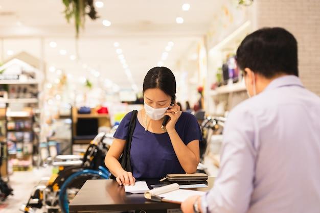 Mulher com máscara protetora, falando no celular.
