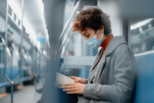 Mulher com máscara protetora lendo livro em um trem do metrô