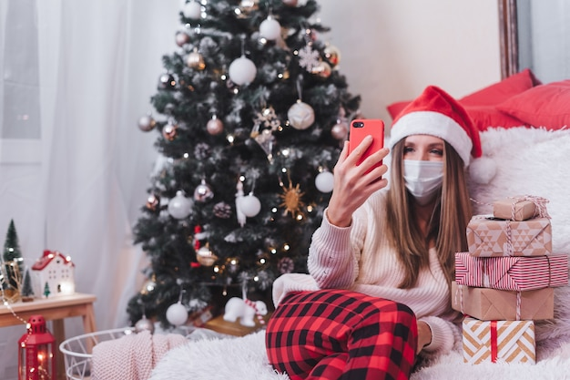 Mulher com máscara protetora médica com caixa de presente, tendo um bate-papo por videochamada no smartphone