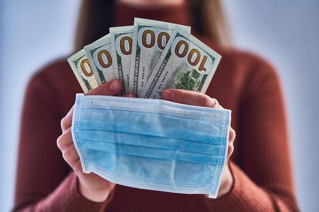 Mulher com máscara protetora médica detém notas de dólar durante o surto de gripe, vírus epidêmico e doenças infecciosas de coronavírus