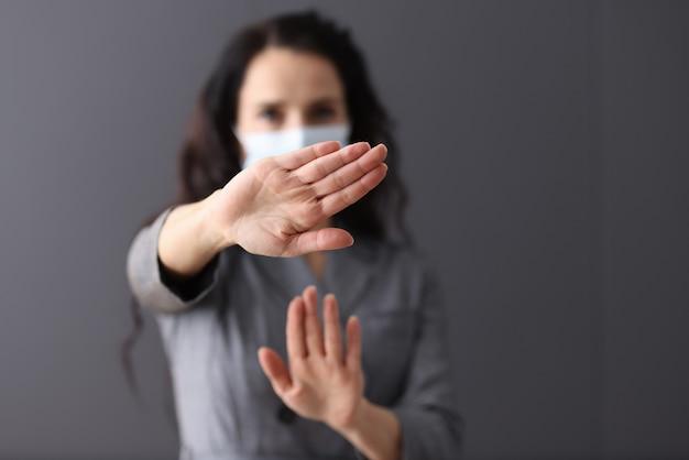 Mulher com máscara protetora médica mantém as mãos em gesto negativo. distância segura no conceito de pandemia de coronavírus