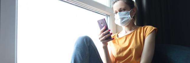 Mulher com máscara protetora médica sentada no parapeito da janela com o celular nas mãos