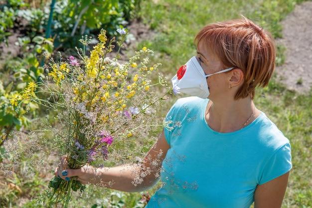 Mulher com máscara protetora segurando buquê de flores silvestres e tentando lutar contra alergias ao pólen.