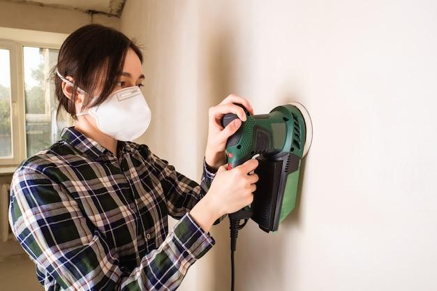 Mulher com máscara protetora trabalhando com lixadeira elétrica para alisar a superfície da parede de gesso, conceito de renovação de sala