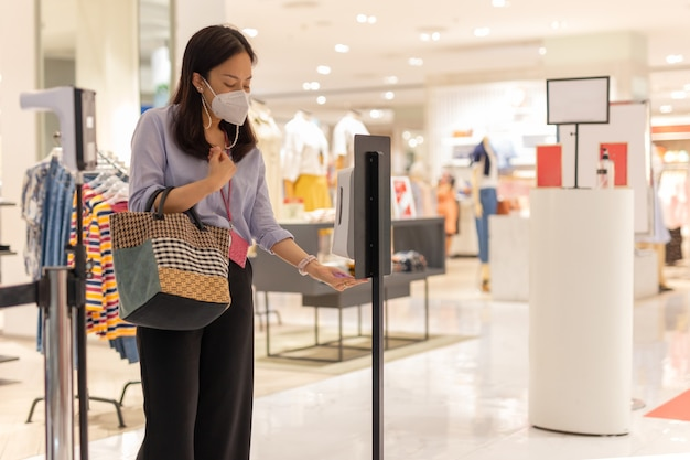 Mulher com máscara protetora usando gel de álcool automático, limpando a mão antes de entrar no shopping