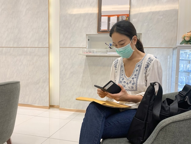 Mulher com máscara protetora usando smartphone