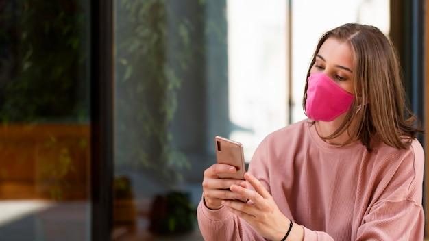 Mulher com máscara rosa segurando o smartphone