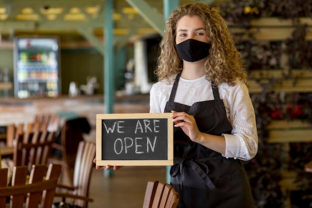 Mulher com máscara segurando uma lousa com placa aberta