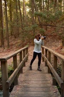 Mulher com máscara tirando fotos em uma ponte em uma floresta