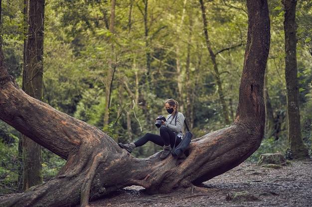 Mulher com máscara tirando fotos no tronco de uma árvore