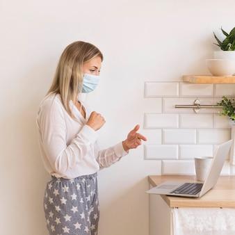 Mulher com máscara trabalhando em casa