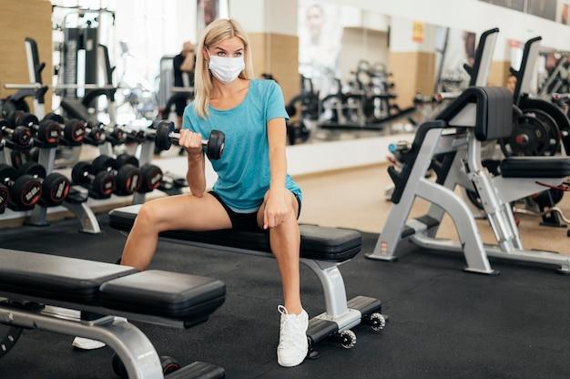 Mulher com máscara treinando na academia durante a pandemia