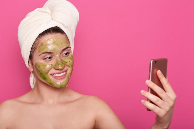 Mulher com máscara verde no rosto, toalha branca enrolada, posa seminua, tomando selfie no smartphone no banheiro