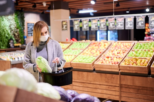 Mulher com máscaras médicas faz compras em um supermercado durante a pandemia de vírus