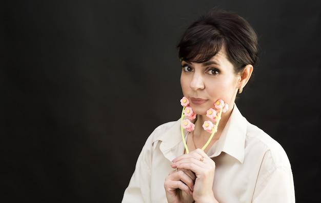 Mulher com massageador facial rejuvenescimento da pele devido a rugas e envelhecimento