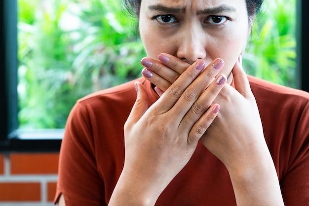 Mulher com mau hálito, cobrindo a boca