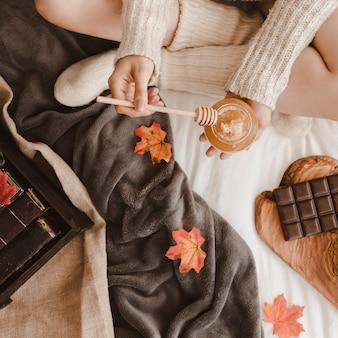 Mulher com mel perto de livros e chocolate