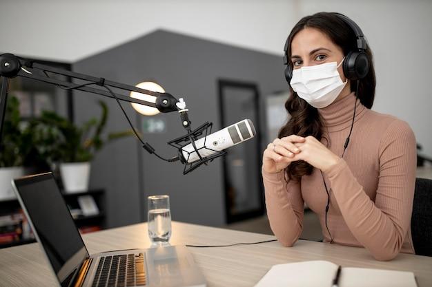 Mulher com microfone e máscara médica em um estúdio de rádio