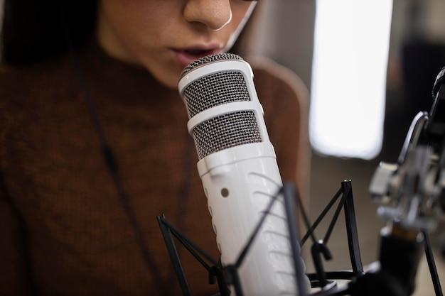 Mulher com microfone fazendo um programa de rádio