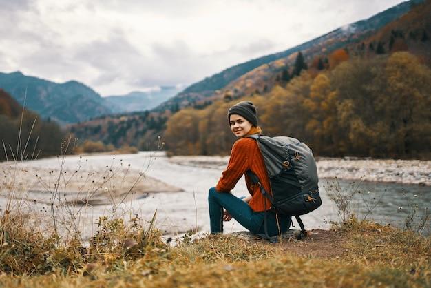 Mulher com mochila à beira do rio paisagem montanhosa outono modelo de grama seca