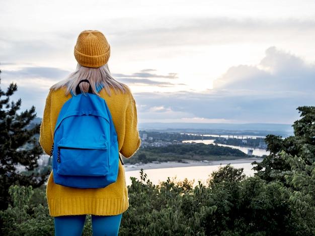 Mulher com mochila, admirando a vista para a montanha