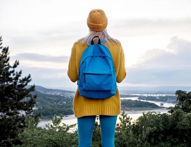 Mulher com mochila, admirando a vista