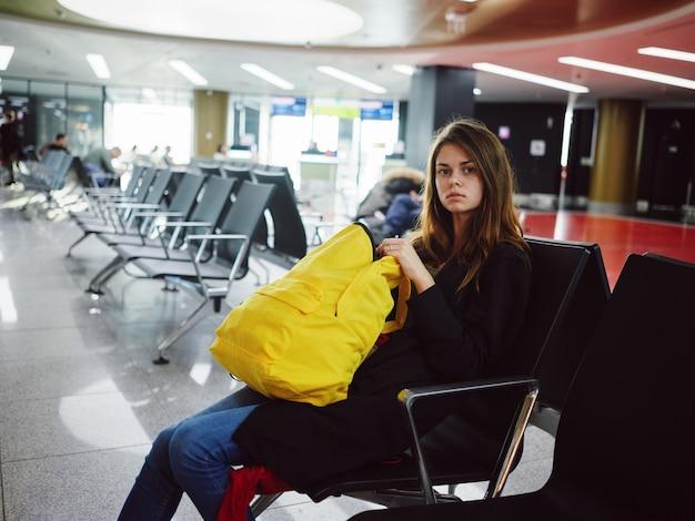 Mulher com mochila amarela sentado no atraso de espera do aeroporto. foto de alta qualidade