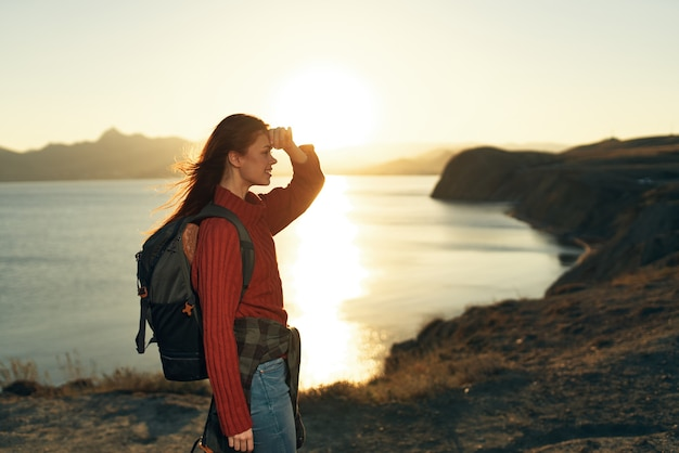Mulher com mochila ao ar livre e montanhas rochosas viajando com ar puro