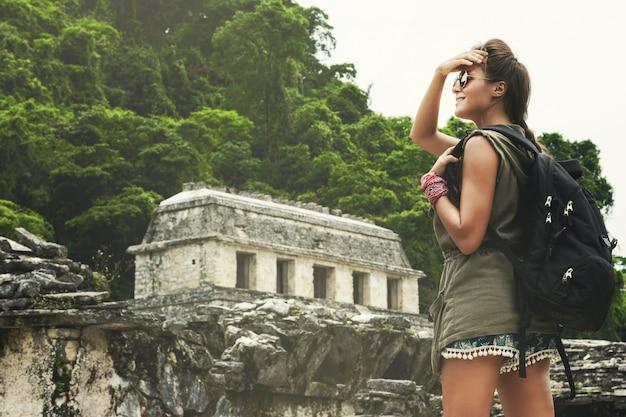 Mulher com mochila ao lado de antigas ruínas maias