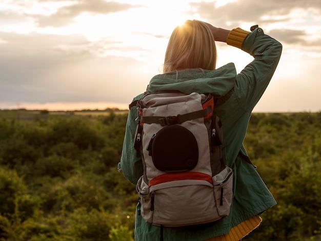 Mulher com mochila ao pôr do sol viajando