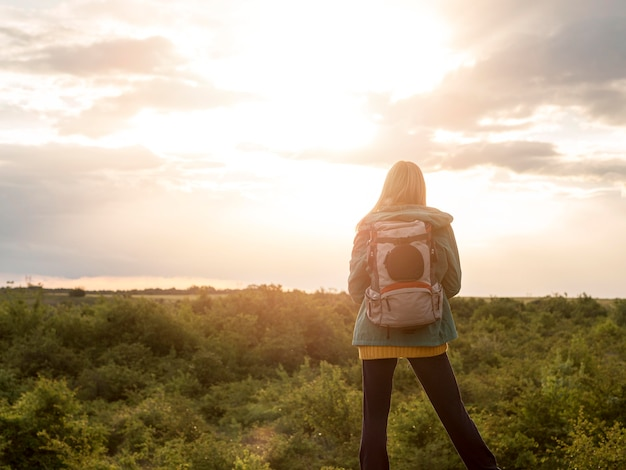 Mulher com mochila ao pôr do sol
