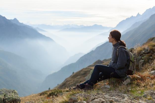 Mulher com mochila apreciando o pôr do sol no pico da montanha nevoenta. montanha alpina com espaço de cópia