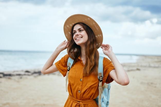 Mulher com mochila caminhando na praia e chapéu vestido de verão