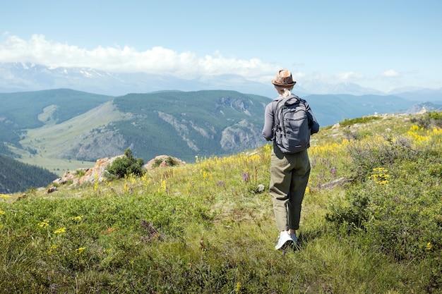 Mulher com mochila caminhando nas montanhas