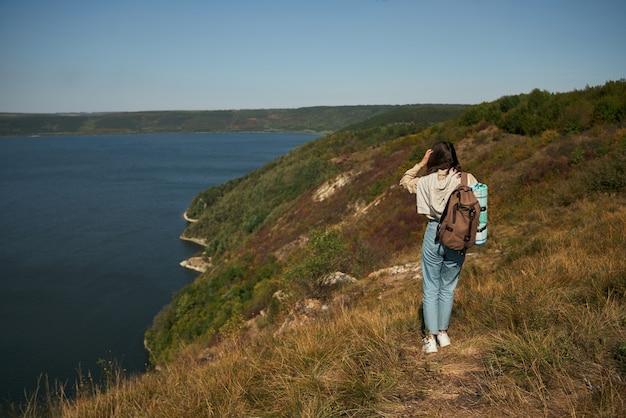 Mulher com mochila caminhando pela alta colina verde