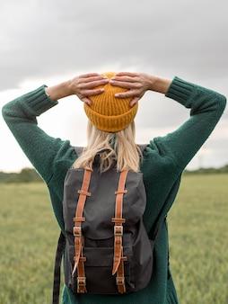 Mulher com mochila, curtindo a natureza