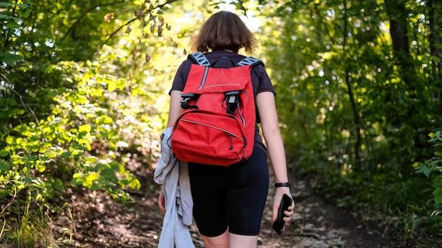 Mulher com mochila de caminhada em uma trilha em uma floresta