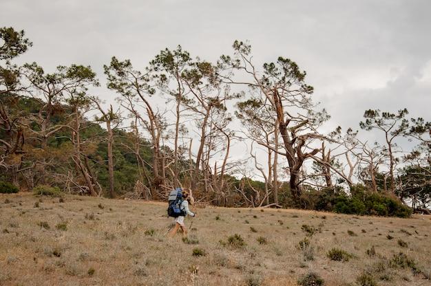 Mulher com mochila e bengalas andando pelo campo seco