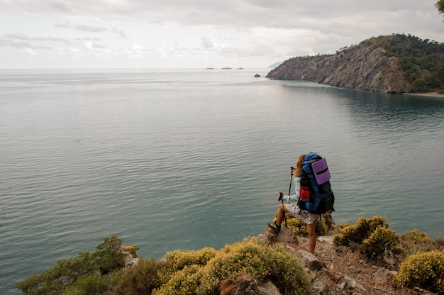 Mulher com mochila e bengalas em pé na colina rochosa
