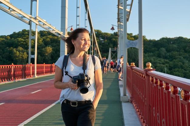 Mulher com mochila e câmara fotográfica