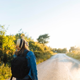 Mulher com mochila e chapéu, admirando a natureza e o sol