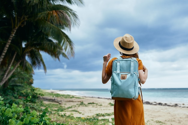 Mulher com mochila e chapéu, areia, praia, ilha, árvores altas no mar