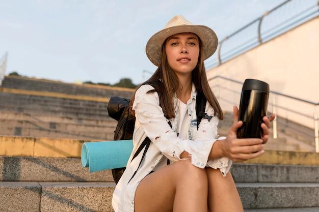 Mulher com mochila e chapéu segurando uma garrafa térmica enquanto viaja